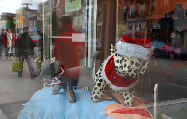 On display in a shop window are a stuffed toy cat and dog are dressed for Christmas.  THe dog is wearing a Santa hat.  Reflected in the window are people passing by carrying shopping bags.