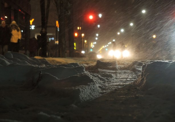 Ruts in the snow on King St. reflect the light from the street lights.  Snow is blowing across the road.  There is a red stop light in the distance, and you can see the headlights of the cars that are stopped for it.