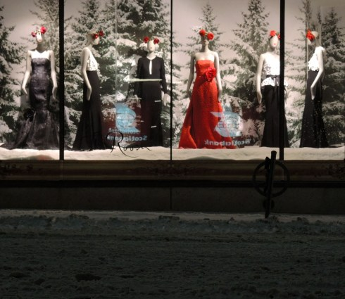 A shop window with 6 mannequins.  They are all dressed in long dresses or black skirts except one of the mannequins who is wearing a red dress.  They all have large red bows in their hair.  The backdrop makes it look that they are standing in a snowy pine forest.