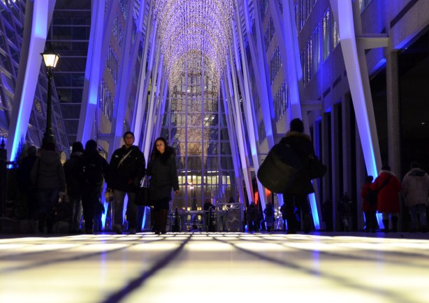 Large, high ceilinged atrium space in a building.  It is lit with purple spot lights. Some people are walking through the space.