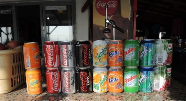 a line up of soft drink cans that are available for sale at a roadside fast food place in Turkey