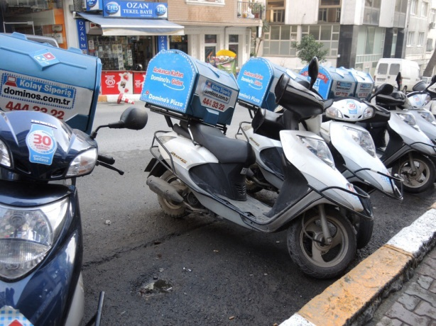 A row of motorcycles with Dominos Pizza delivery boxes on the back of them.