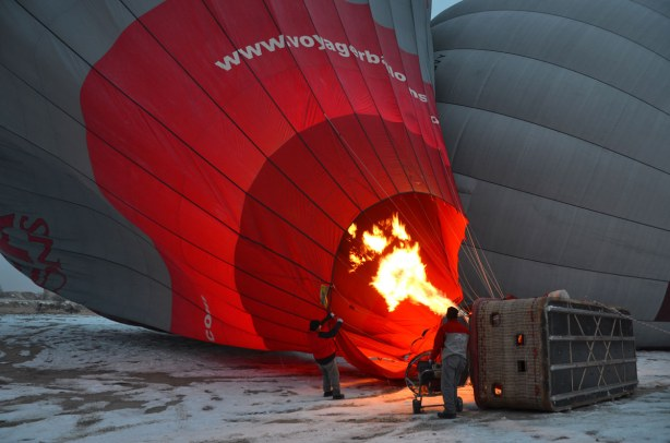 A large red and grey hot air balloon is lying on its side while two men heat the air to fill the balloon.  Large flames can be seen.