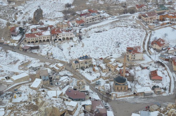 bird's eye view of a town in the winter showinh roads, houses and mosques
