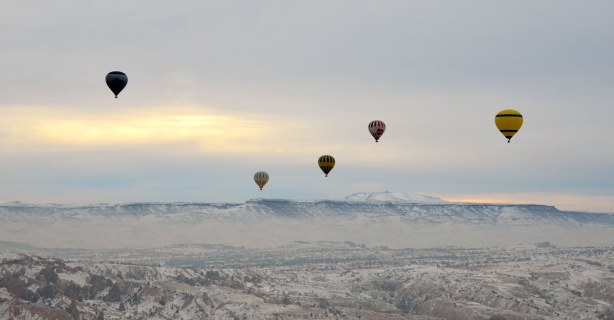 Five or six hot air balloons in the distance, all flying over a valley with mountains in the background.