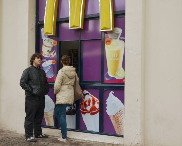 Two people waiting for their order at a McDonalds with a walk up window where you can buy your food without having to go inside.