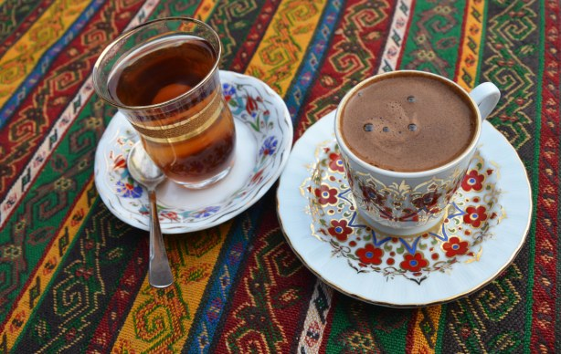 Apple tea in a glass cup and turkish coffee in a china cup and saucer, on a table with a brightly coloured striped table cloth in reds, greens and gold.