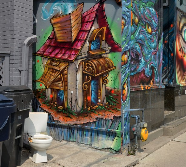 A white toilet sits on a sidewalk outside of a house.  On the side of the house, just behind the toilet, is a painting of a an old house.