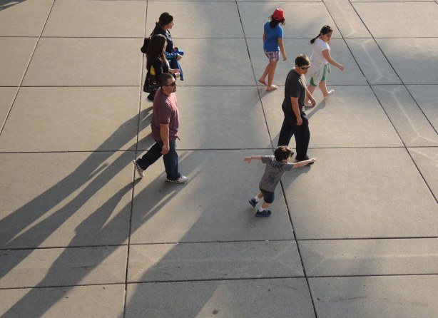 A group of people walking across Nathan Phillips square.  They are walking on crete and the afternoon shadows are long.