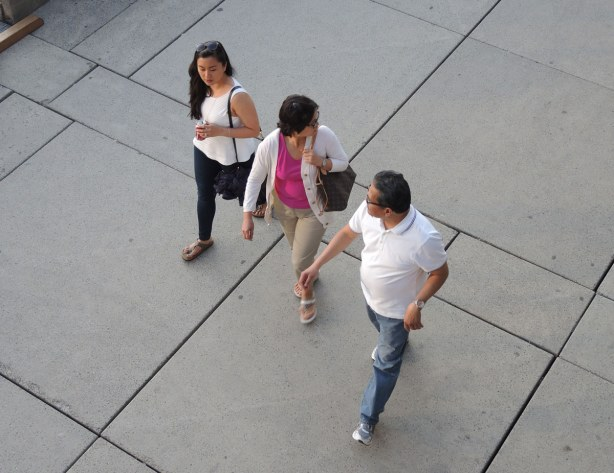 A group of three people walking across Nathan Phillips square.  They are walking on crete and the afternoon shadows are long.