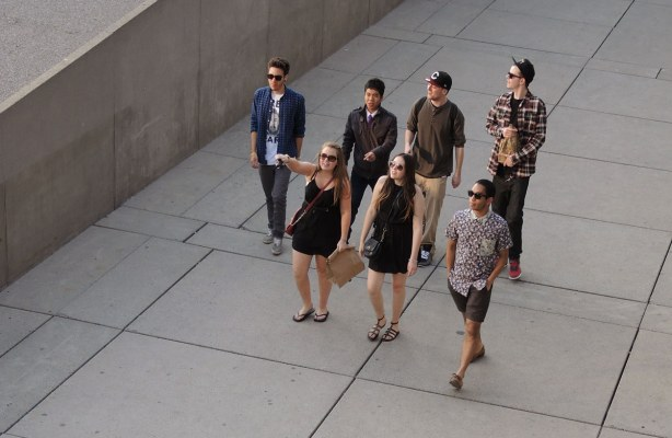 A group of young people walking across Nathan Phillips square.  They are walking on concrete.  Five guys and two girls.  Both girls are in short black dresses with black sandals.