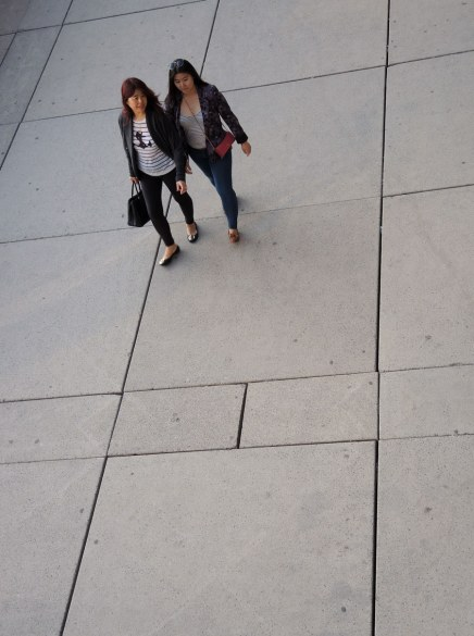 Two women are walking on the concrete squares