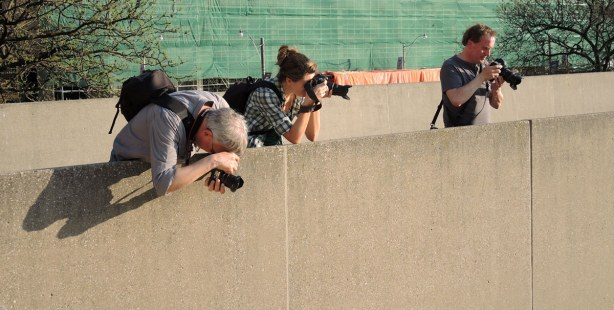 Three photographs are shooting from behind a low concrete wall.  One has his camera aimed downwards towards the people walking below.  The others have their cameras aimed farther out.