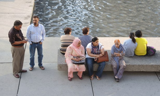 A group of people are either sitting on a bench, or standing beside it, in Nathan Phillips Square, beside the fountain pool