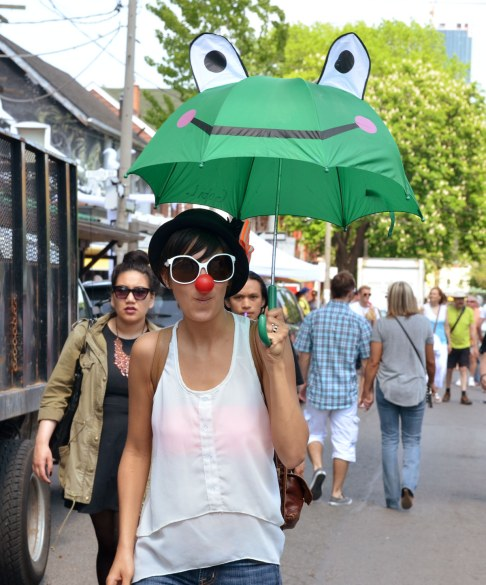 A woman has a large fake red nose and large white frames sunglasses.  She is carrying a green umbrella with a froggie face on it