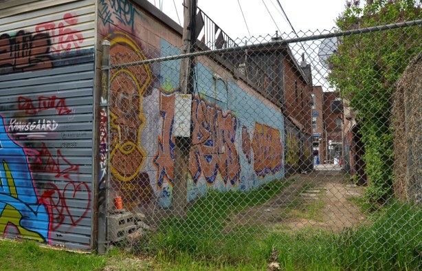 Looking through a chain link fence towards a short laneway.  There is graffiti on the walls of the buildings that back onto the alley