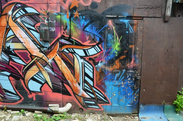 Multicoloured graffiti that covers a door as well as the wall.