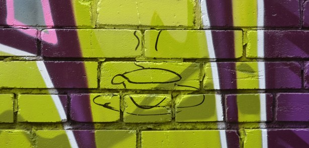 black outline picture of a tea cup and saucer, with steam rising from it, on top of green and purple graffiti