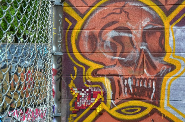Graffiti of a pinkish face with bared teeth.  CHainlink fence on the left of the photo.