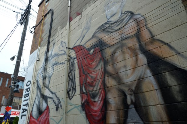 Street art piece of a semi clad woman and a male nude, reaching for each other.  They are larger than life, and higher up on a wall.