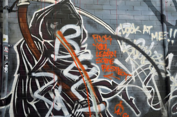 A graffiti piece of a black hooded figure.  Someone has tagged over part of it in large white letters.  The next person has put an orange line through the white tags and then added the words  Fuck You learn some respect