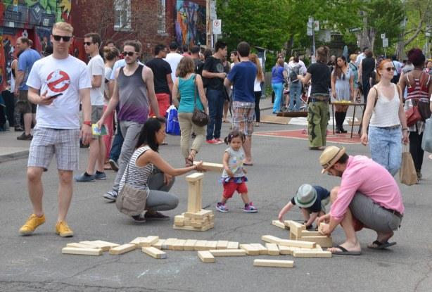 A pile of large wood blocks are in the middle of the street and a family is building small towers with them - a small girl and boy and their parents.