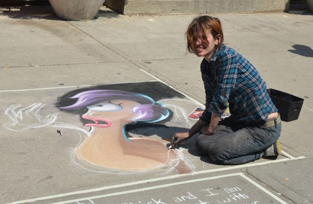A young woman is sitting on the sidewalk.  She is creating a picture of one of the characters from the TV show Futurama.
