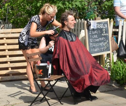 a man is getting his hair cut outside