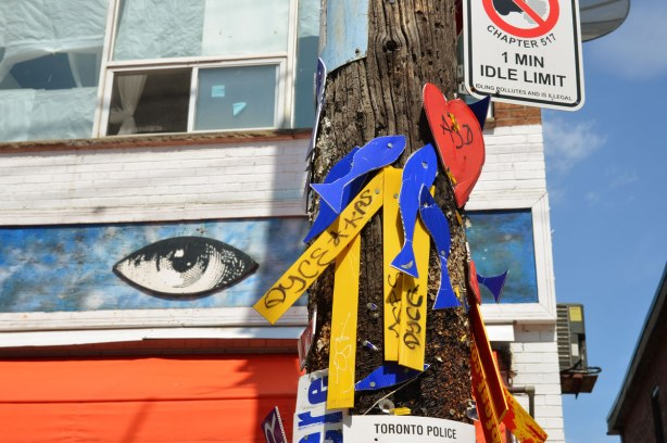 Detail of messages attached to a telephone pole.  They are written on strips of yellow and blue heavy paper.  In the background is a painting of a large eye, part of the sign above the door of Orbital Arts on Augusta Ave.