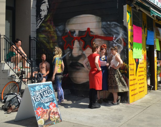 Some people sitting on steps, three women standing in front of a large graffiti face that is wearing large star shaped sun glasses.