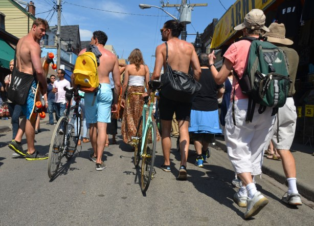 A group of young people are walking down the street, away from the camera. Some are walking their bikes and some of the men are topless.