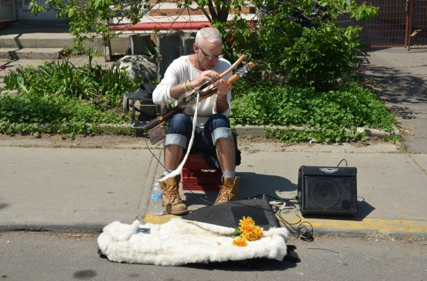 A man sitting on a stool on the sidewalk, playing a musical instrument