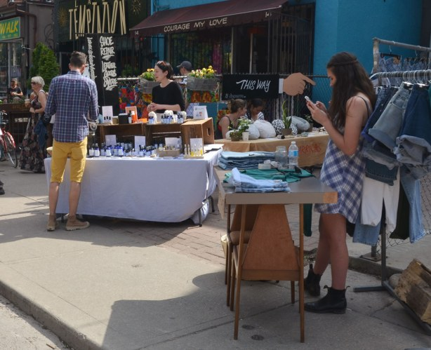 A woman is looking at her phone as she waits behind a table where she is selling denim shorts (on the sidewalk).  In the background a man is buying something at another vendor's table.