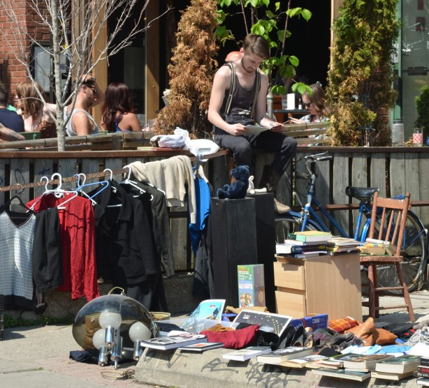 A man is sitting on a fence reading a book.  There are books on the ground in front of him that are for sale.  There are also some shirts on hangers that are for sale.