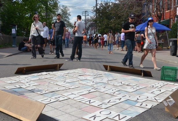 People are walking towards the camera, down the street, but between them and the camera is a giant scrabble game that is now finished