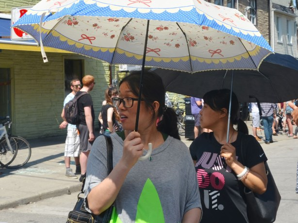 Two women, each with an umbrella open above their heads are standing in the street.