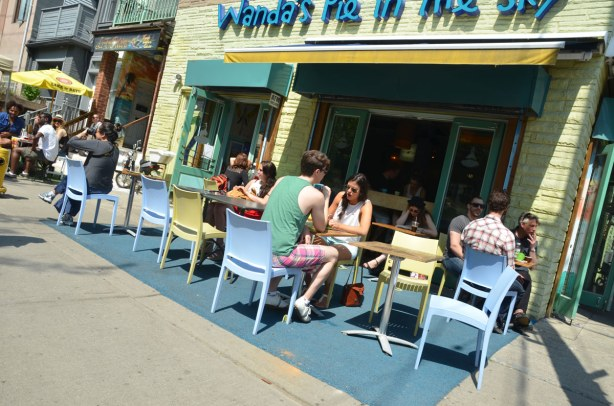 The front of Wandas Pie in the Sky restaurant.  People are sitting at tables and chairs set up outside the restaurant.
