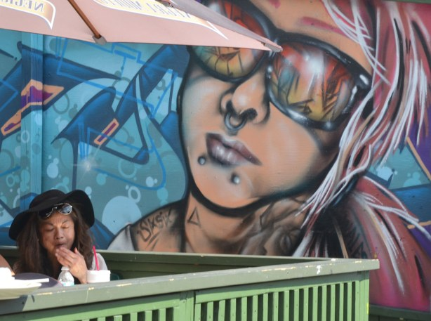 A woman is sitting at a table, under a patio umbrella.  Behind her is a large graffiti piece of a young woman's face