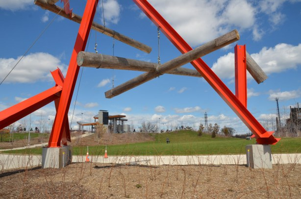 Part of a large red metal sculpture is in the foreground, looking past it you can see the pavillaion on top of a small hill that is part of Corktown Common park