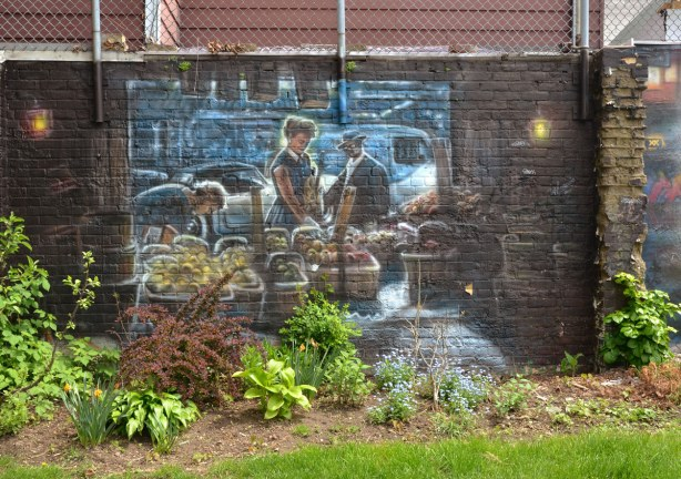 mural on a brick wall depicting a scene from a visit to Kensington Market , people buying fruit and vegetables from a street vendor.  Spring plants are growing in front of the wall.