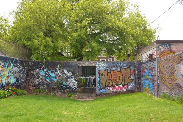 A brick wall that runs across the back of the park. It is covered with graffiti.  There is a metal gate in the center and you can see that there is  more graffiti on the walls of the alley behind.