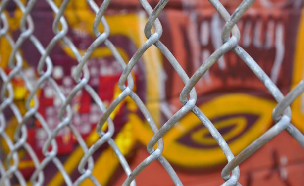A chain link fence in front of a piece of graffiti in oranges, yellows and purple