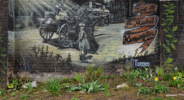 Spring plants are growing in front of the wall on which there is a mural on a brick wall depicting a scene from a visit to Kensington Market circa 1885.  A small girl is standing beside a cart.