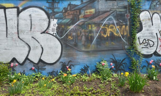Large white tags obscure part of a mural depicting Kensington market in the past