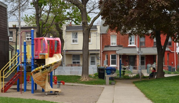 A play structure with slide is on the left of the picture, a woman is sitting on a bench on the right side.  Row houses on the opposite side of the street can also be seen.  There are some large trees too.