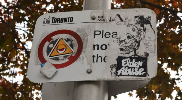 A city of Toronto sign that has had four stickers attached to it.
