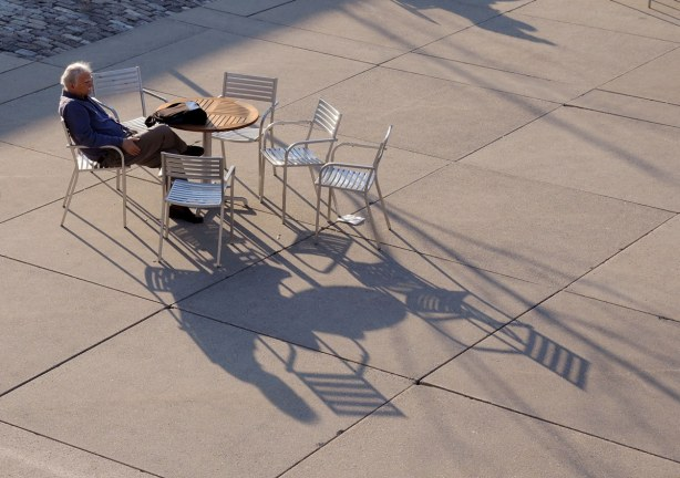 A man is sitting at a table outside, on Nathan Phillips Square, late afternoon, with long shadows making patterns on the concrete