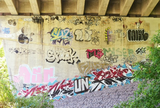 tags and a few small pictures on a large concrete support at one end of theBathurst St. over Cedarvale Park,graffiti under the bridge
