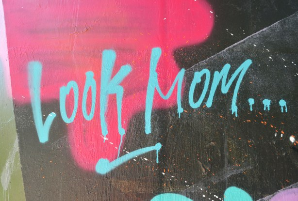 bright blue words 'Look Mom' on pink and black, Bathurst St. over Cedarvale Parkgraffiti under the bridge