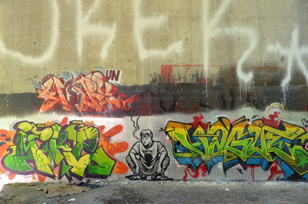 three large colourful tags and one grey scale picture of a man squatting and smoking a cigarette,Bathurst St. over Cedarvale Park, graffiti under the bridge